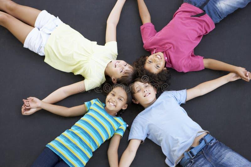 Obenliegende Ansicht der Gruppe Kinder, die zusammen auf Trampoline liegen stockfotografie