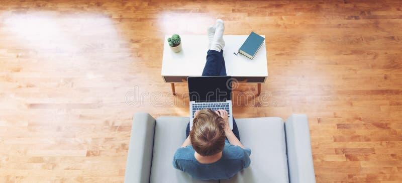 Obenliegende Ansicht der jungen blonden Person, die auf Laptop schreibt lizenzfreie stockfotografie