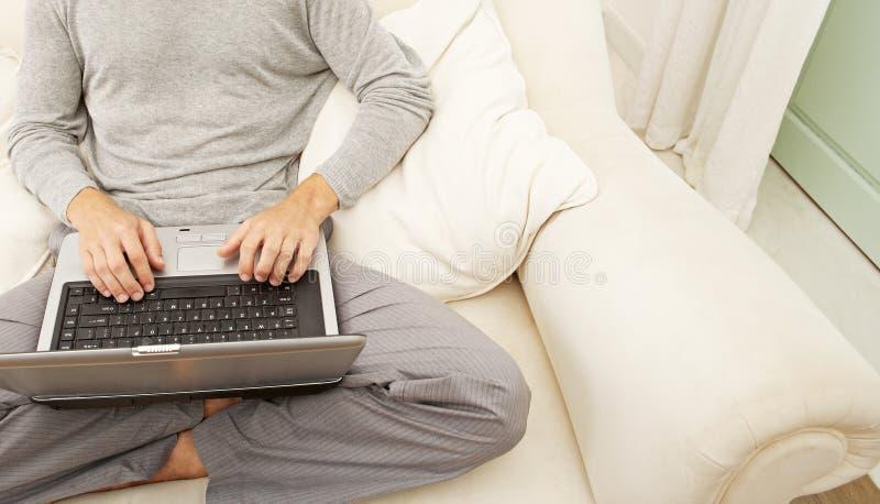 Obenliegende Ansicht des Berufsmannes mit Laptop und intelligentem Telefon zu Hause. stockfotos