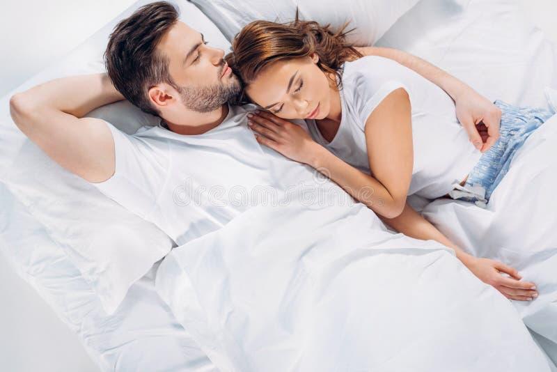 obenliegende Ansicht des jungen Paarschlafens lizenzfreie stockfotos