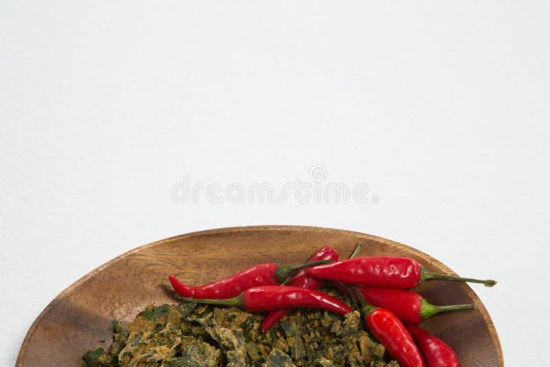 Obenliegende Ansicht des Pfeffers des roten Paprikas und des getrockneten Kohls in der hölzernen Platte lizenzfreie stockfotografie