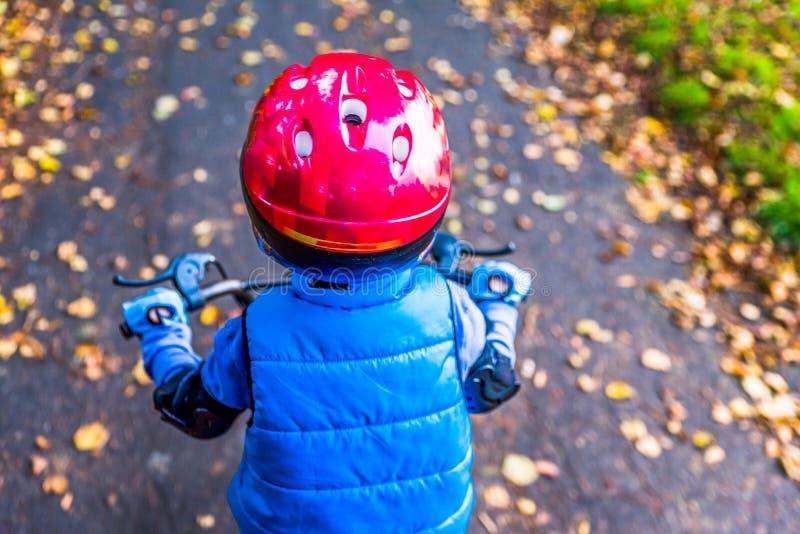 Obenliegende Ansicht eines Jungenreitfahrrades mit Schutzhelm draußen am Herbstpark stockfotos
