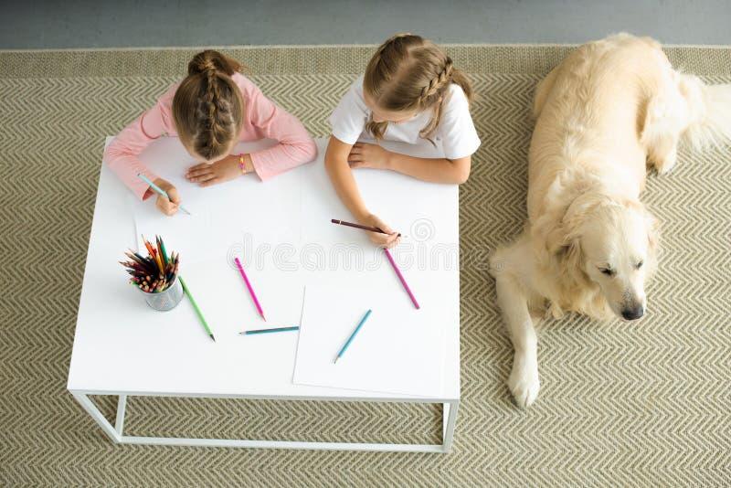 obenliegende Ansicht von den kleinen Schwestern, die bei Tisch Bilder mit dem golden retriever-Hund nahe stillsteht auf Boden zei stockfotos