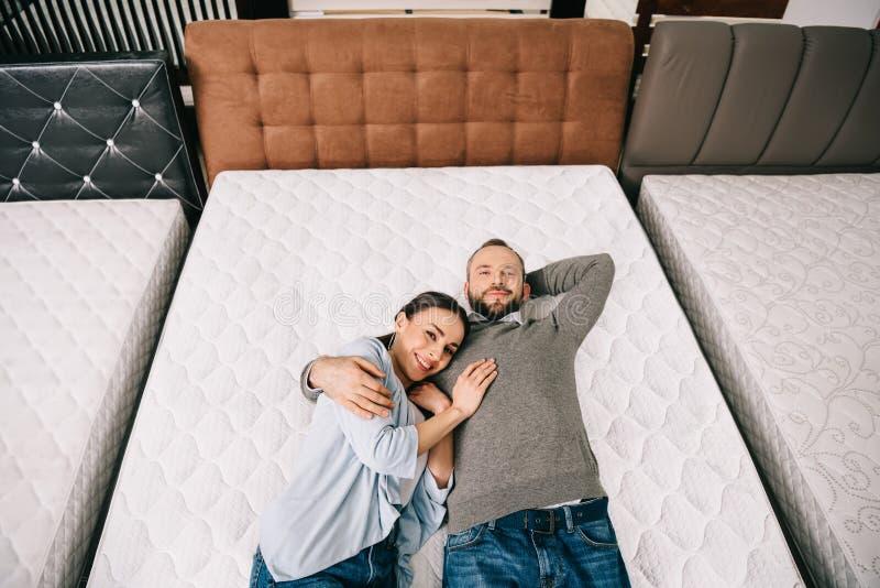 obenliegende Ansicht von den lächelnden Paaren, die auf Bett im Möbelgeschäft liegen stockbilder