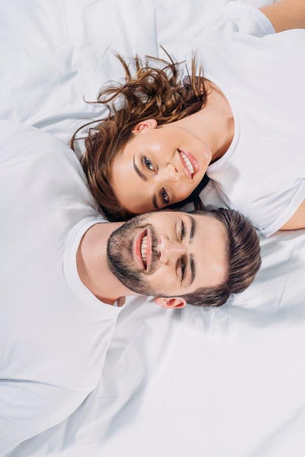 obenliegende Ansicht von jungen lächelnden Paaren in der Liebe, die Kamera beim Lügen betrachtet lizenzfreie stockfotos