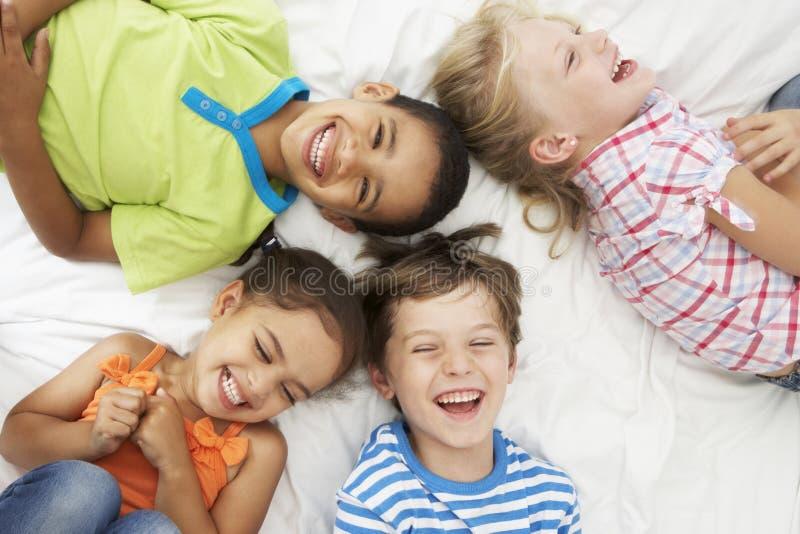 Obenliegende Ansicht von vier Kindern, die zusammen auf Bett spielen stockbild