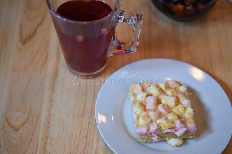 Obenliegende Ansichtlebensmittelphotographie eines selbst gemachten Eibischkuchens mit heißem rotem Fruchtglas Tee auf hölzernem  stockbilder
