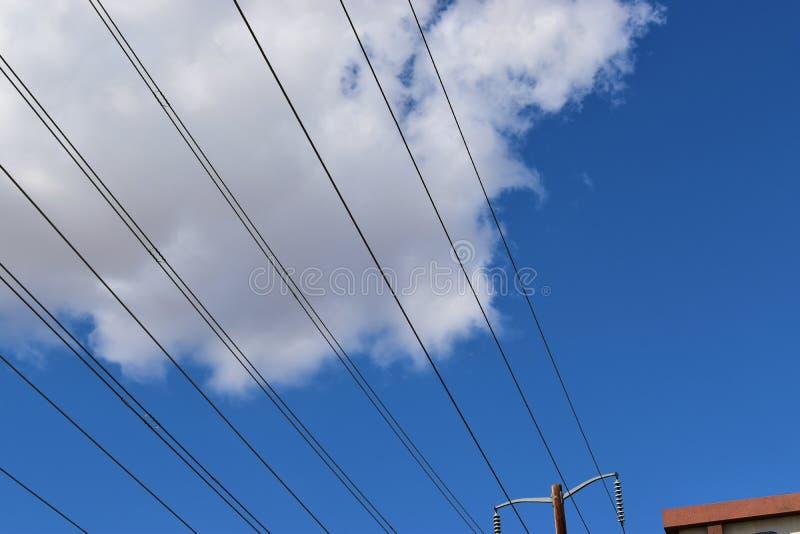 Obenliegende Energiedrähte gegen einen weißen Wolkenhintergrund lizenzfreies stockbild