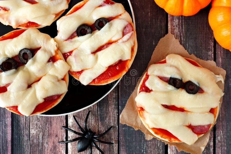 Obenliegende Szene der Halloween-Mamaminipizzas auf rustikalem Holz lizenzfreie stockbilder