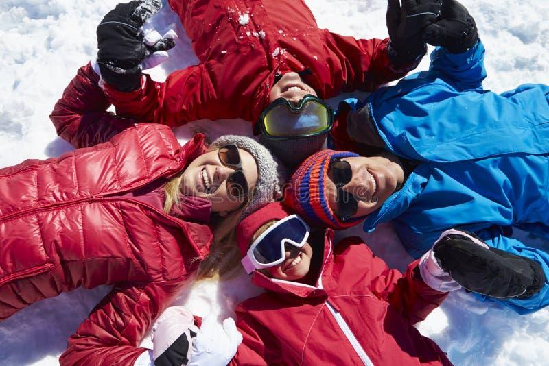 Obenliegender Schuss der Familie, die Spaß auf Winterurlaub hat lizenzfreies stockbild