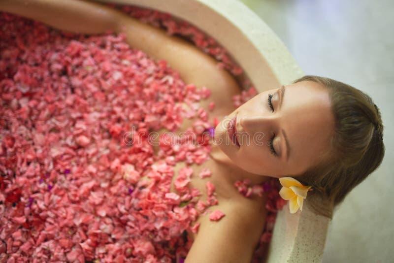 Obenliegender Schuss der natürlichen tausendjährigen Frau in der luxuriösen Badekurortbadewanne gefüllt mit den Blumenblumenblätt stockfotos