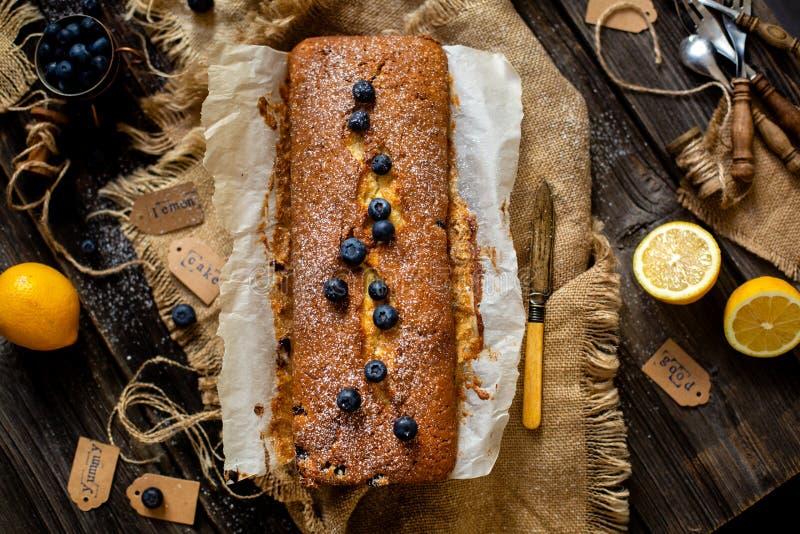 Obenliegender Schuss des selbst gemachte geschmackvolle Zitrone gebackenen Kuchens mit Blaubeeren auf Papier und Sackleinen stockfoto