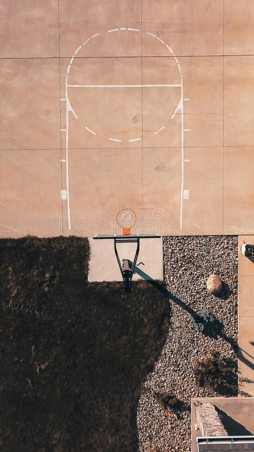 Obenliegender Schuss eines Zementbasketballfeldes mit dem Band und den Felsen lizenzfreies stockbild