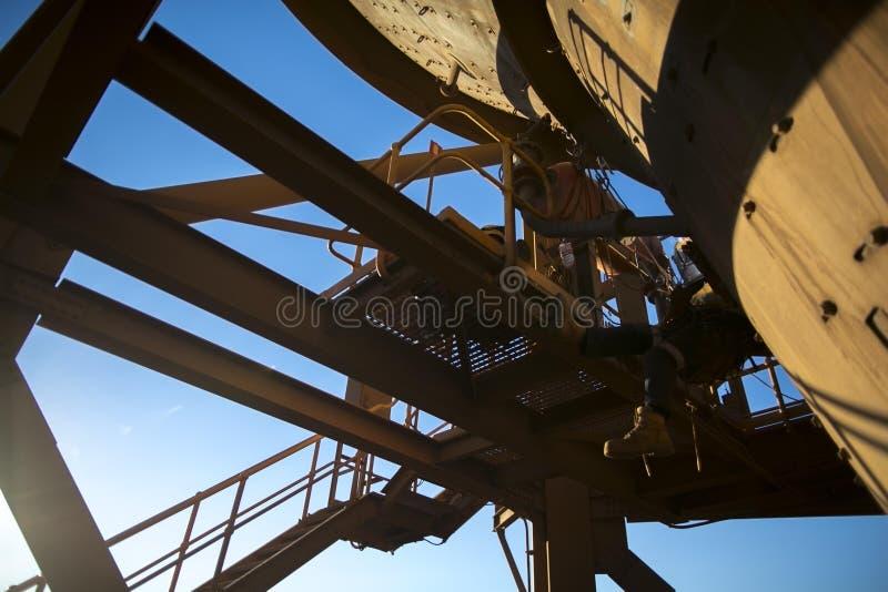 Obenliegender Schuss industriellen Seilzugang abseiler Schweißers, der an den Höhenwartungsdienstleistungen arbeitet stockbilder