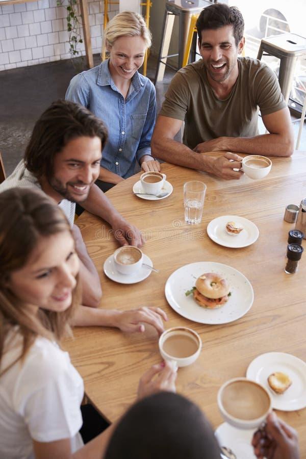 Obenliegender Schuss von den Freunden, die für das Mittagessen in der Kaffeestube sich treffen stockfoto