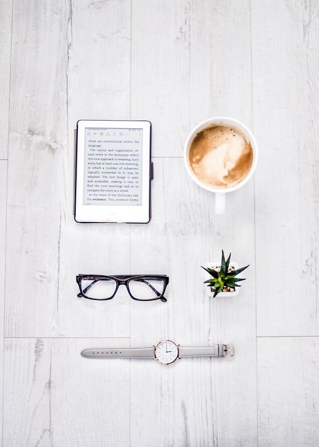 Obenliegender Schuss von zünden, Kaffee, Gläser, ein Pflänzchen und Uhren auf einer Holzoberfläche an lizenzfreies stockbild