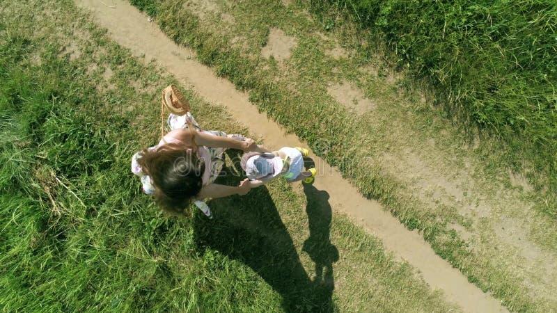 Obenliegender von der Luftschuß der Mutter und ihres wenig Kinderspiels der zusammen und Drehbeschleunigung um Händchenhalten stockfotos