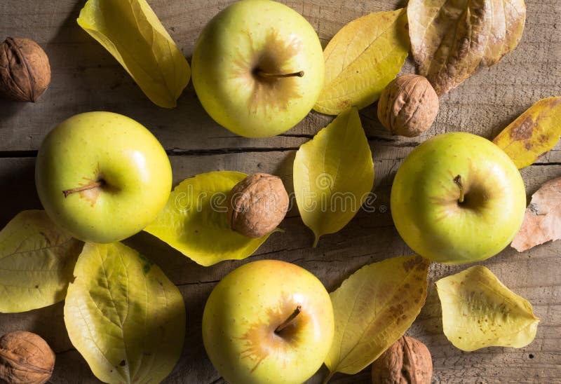 Obenliegendes Foto von Äpfeln, von Walnüssen und von Herbstlaub auf rustikalem Holz stockfoto