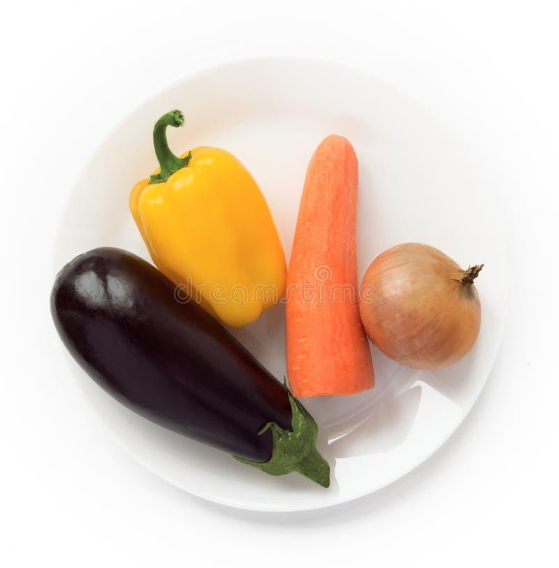 Oberżyna, dzwonkowy pieprz, marchewka i cebula na talerzu, zdjęcie stock