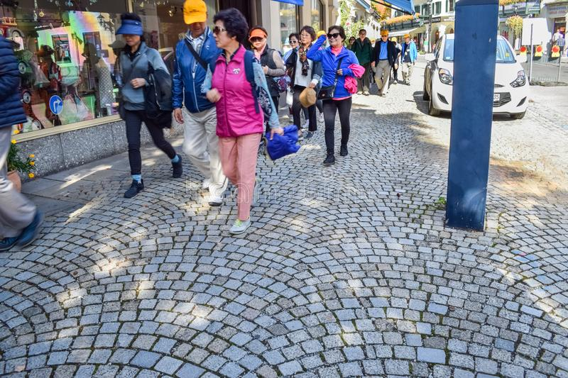 OBERAMMERGAU, GERMANY - OKTOBER 09, 2018: A group of Chinese tourists on a tiled pavement. In Germany, cobblestone, editorial, travel, backpacks, color, crowd stock image