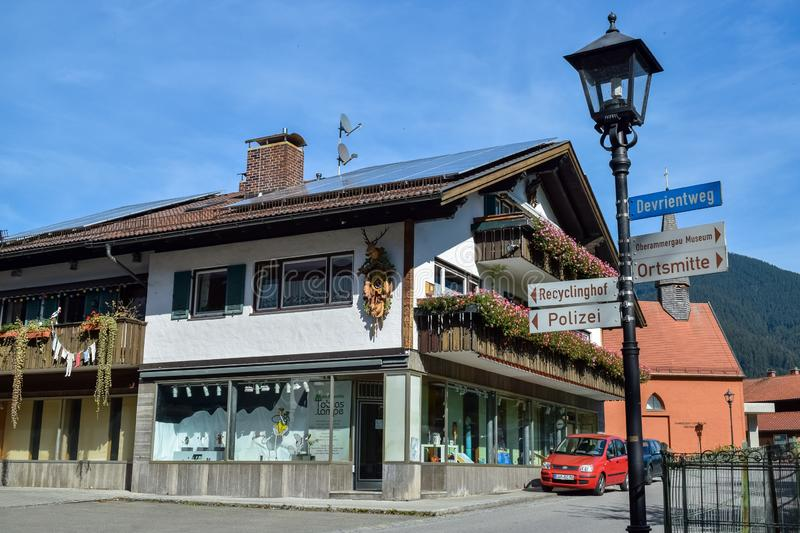 OBERAMMERGAU, GERMANY - OKTOBER 09, 2018: Old lamppost with direction signs and an old building with balconies on street royalty free stock photography