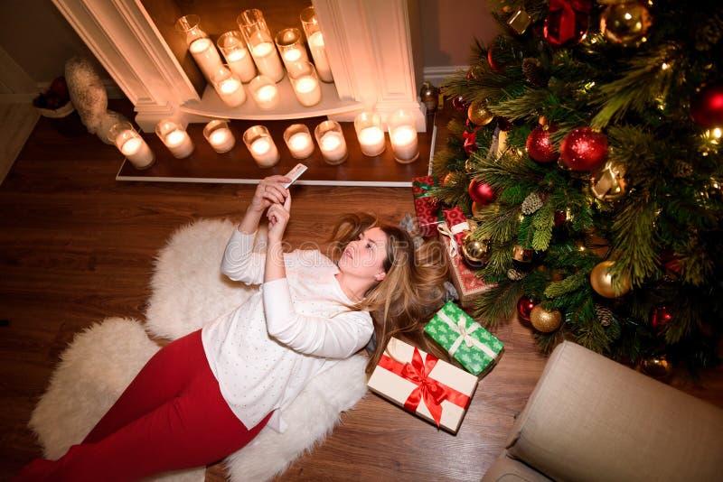 Obere Ansicht über ein Mädchen, das unter einem Weihnachtsbaum liegt stockbild