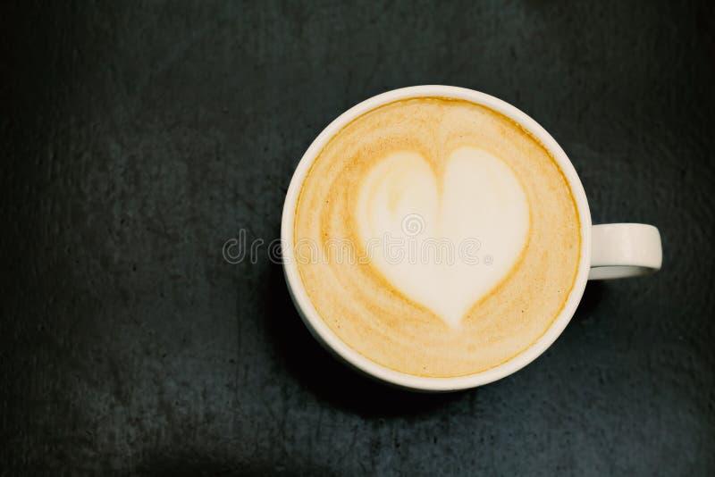 Obere Aussicht auf große Tasse frisch gebrühtem Cappuccino mit weichem Schaum und Herz auf Holztisch lizenzfreies stockfoto