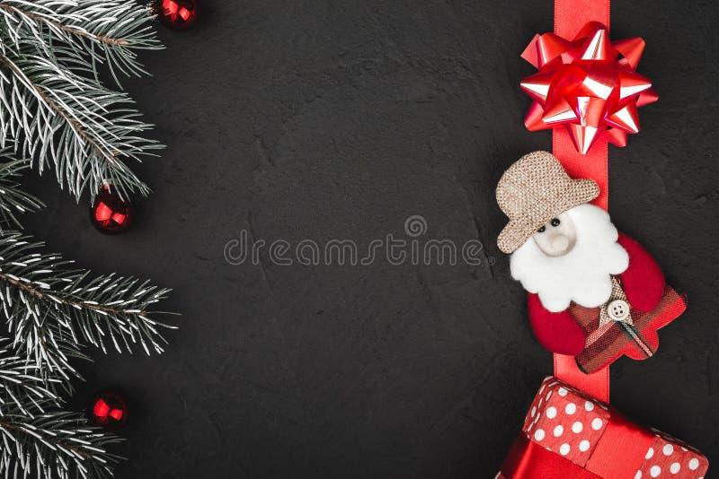 Obere Draufsicht eines roten Bandes, Geschenk, handgemachtes Sankt-Spielzeug und Immergrün verzweigen sich auf einen schwarzen St lizenzfreie stockbilder