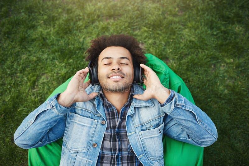 Oberes Ansichtporträt des erfreuten entspannten Afroamerikanermannes mit der Borste, die auf Gras während hörende Musik mit liegt lizenzfreies stockbild
