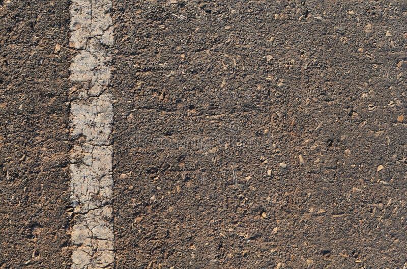 Oberfläche der defekten Asphaltstraße in der Landschaft stockbilder