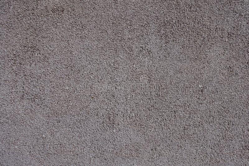 Oberfläche der gemalten körnigen graulichen rosa Wand stockfotografie