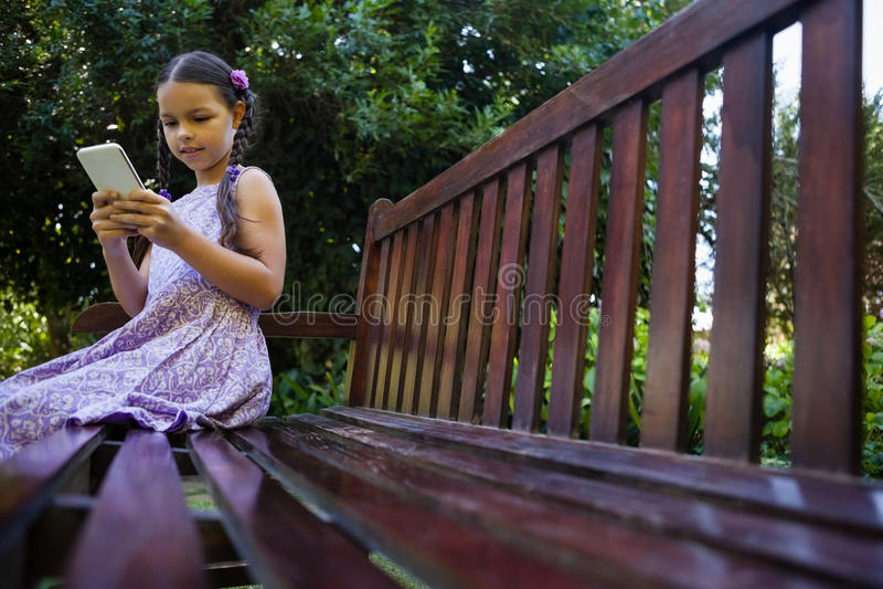 Oberflächenniveau des Mädchens sitzend auf Holzbank bei der Anwendung des Handys lizenzfreie stockfotos