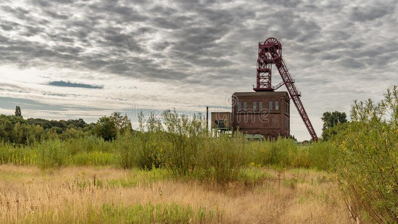 Mining tower in Oberhausen, North Rhine-Westfalia, Germany. Oberhausen, North Rhine-Westfalia, Germany - July 30, 2018: Clouds over a historic mining tower royalty free stock image