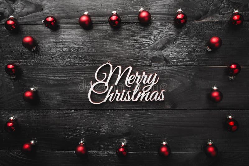 Oberleder, Spitze, Ansicht von oben, von immergrünen roten Spielwaren und von weißer Aufschrift der frohen Weihnachten, auf schwa lizenzfreie stockfotografie