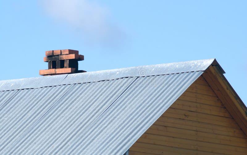 Oberseite des hölzernen Hauses des Landes mit dem Metalldach lizenzfreie stockbilder