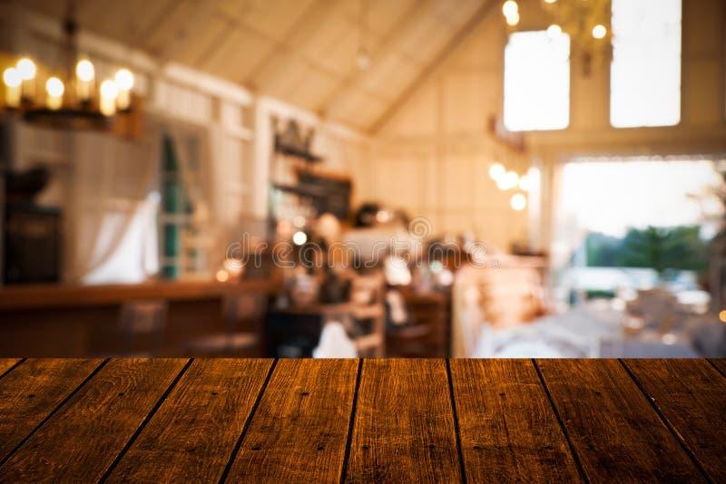 Oberste alte hölzerne Tabelle der Nahaufnahme mit Unschärferestaurant- und -Kaffeestubehintergrund lizenzfreies stockbild