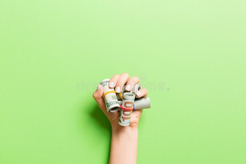 Oberste Ansicht der Dollarnoten, die in Röhren in weiblicher Palme auf grünem Hintergrund aufgewickelt wurden Rentabilitätskonzep lizenzfreie stockfotografie