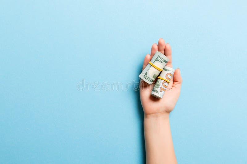 Oberste Ansicht der Dollarnoten, die in Rohren in weiblicher Palme auf blauem Hintergrund aufgewickelt werden Bezugskonzept mit K lizenzfreie stockfotografie