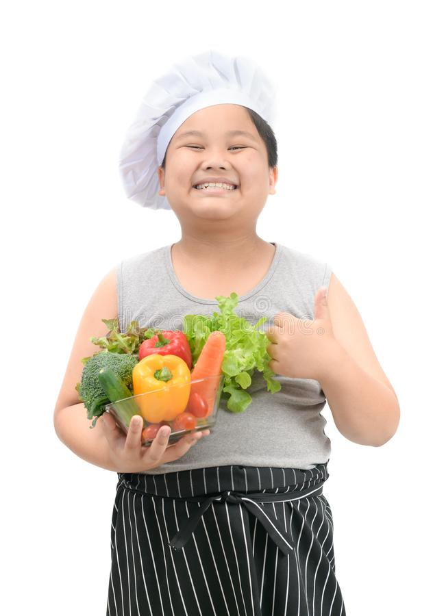 Obese boy chef smaile and like to eat vegetables royalty free stock photos