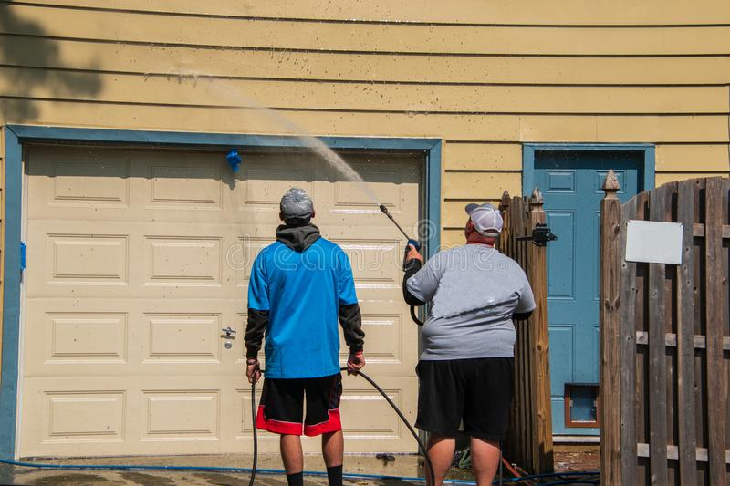 Obese Caucasian man is spray pressure washing the siding on his house. His son is holding the hose and watching royalty free stock photo