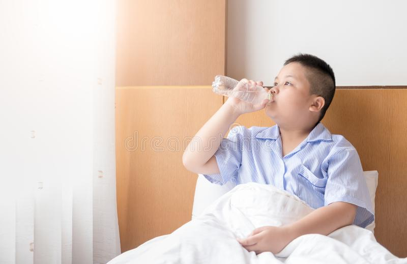 Obese fat boy drinking water on bed in morning royalty free stock photos