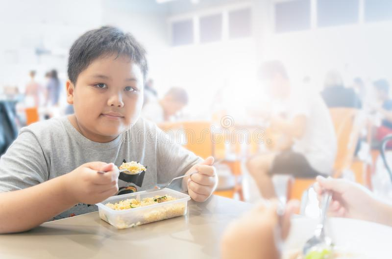 Obese fat boy eating box lunch in food court stock photography