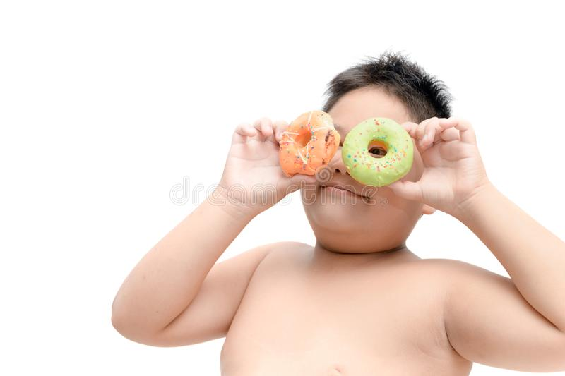 Obese fat boy is eating donut isolated stock images