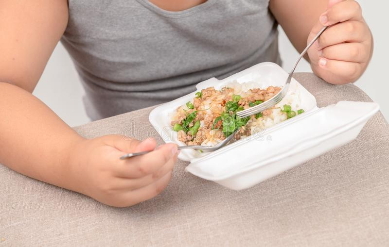 Obese fat boy eating fried rice in foam box royalty free stock photography