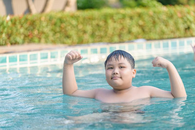 Obese fat boy show muscle in swimming pool stock images