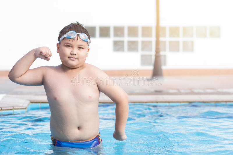 Obese fat boy swimming pool. Obese fat boy in swimming pool, concept healthy and exercise royalty free stock image