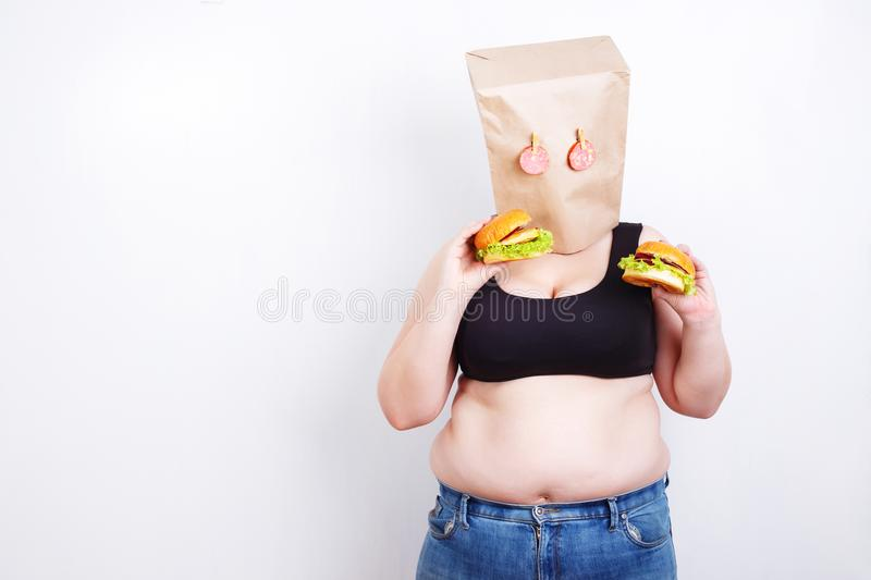 Obese fat woman with a paper bag on head like a mask with eyes. Made of salami as a symbol of food addiction trying to eat a hamburger. Studio shoot with copy stock photo
