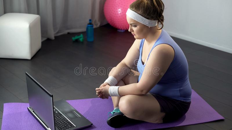 Obese female watching online videos of effective training methods on her laptop stock photo