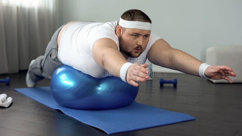 Obese hardworking man practicing static exercise, strength training program. Stock photo royalty free stock photography