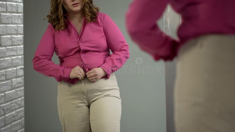 Obese lady buttoning up tight shirt on stomach with effort, overweight problem. Stock photo royalty free stock photo